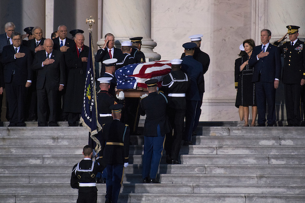 UNITED STATES - DECEMBER 3: The casket of the late George H.W. Bush arrives on the East Front of the Capitol to lie in state in the Rotunda on December 3, 2018. Seen at right is his son, former President George W. Bush, and former First Lady Laura Bush. Also pictured to the left of the casket, from right, are Dan Quayle, James Baker, Colin Powell, and Dick Cheney. He passed away Friday at age 94. (Photo By Tom Williams/CQ Roll Call)