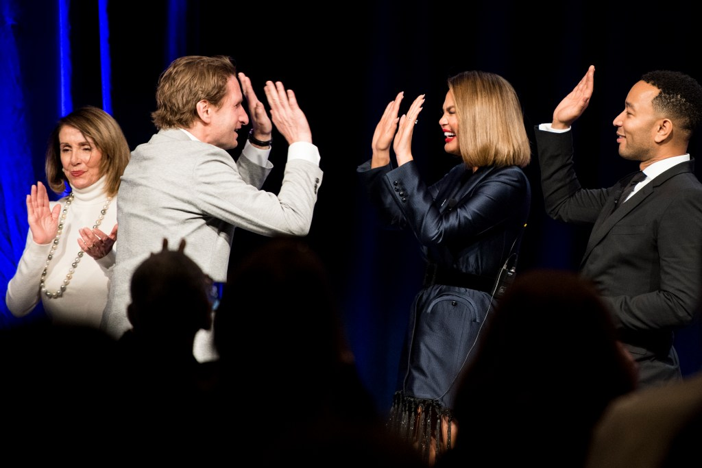 UNITED STATES - APRIL 10: Rep. Dean Phillips, D-Minn., gives model Chrissy Teigen and her husband and singer John Legend high fives on stage at the end of the dinner program at the House Democrats' 2019 Issues Conference at the Landsdowne Resort and Spa in Leesburg, Va., on Wednesday, April 10, 2019. (Photo By Bill Clark/CQ Roll Call)