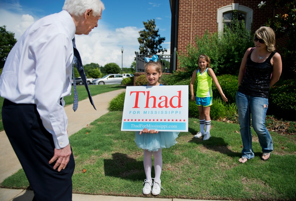 UNITED STATES - MAY 30: Sen. Thad Cochran, R-Miss., greets Claire Webby, 7, as her sister Grace, 9, and mother Laurie look on, upon arriving at City Hall in Olive Branch, Miss., May 30, 2014. (Photo By Tom Williams/CQ Roll Call)