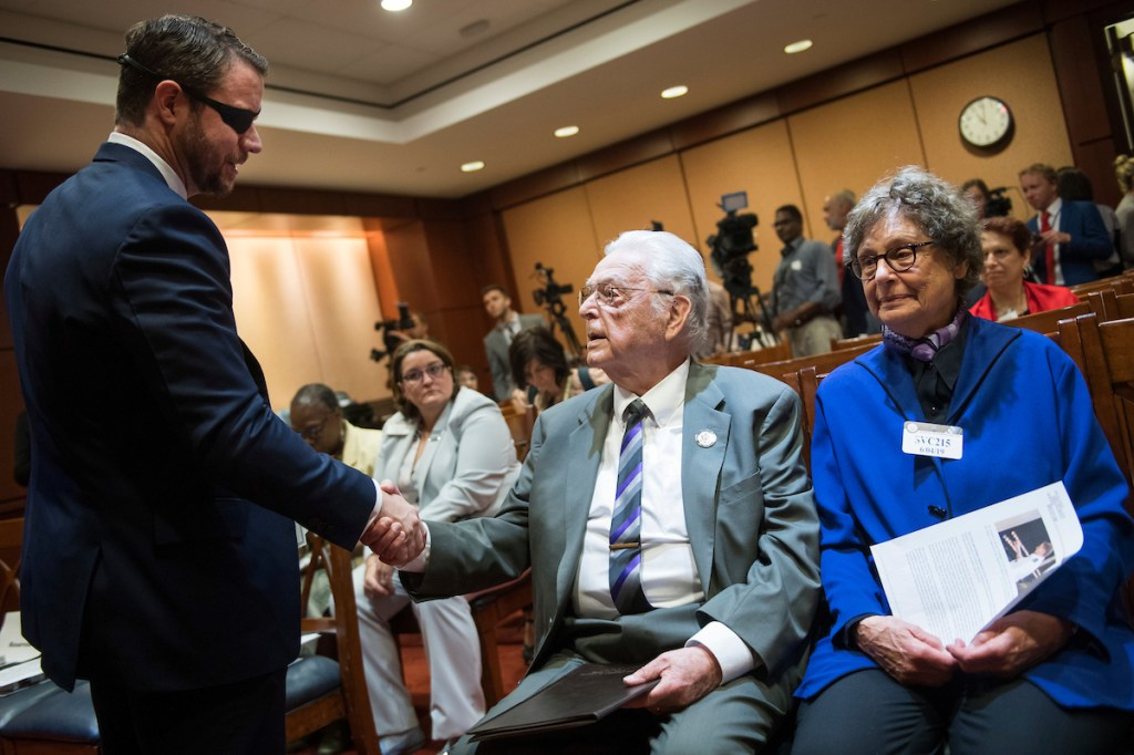 UNITED STATES - JUNE 4: Rep. Dan Crenshaw, R-Texas, greets Holocaust survivor Steven Joseph Fenves of Rockville, Md., and his wife Norma, during an event with the U.S. Holocaust Memorial Museum to honor the 75th anniversary of D-Day in the Capitol Visitor Center on Tuesday, June 4, 2019. Fenves was born in Yugoslavia on June 6, 1931. (Photo By Tom Williams/CQ Roll Call)
