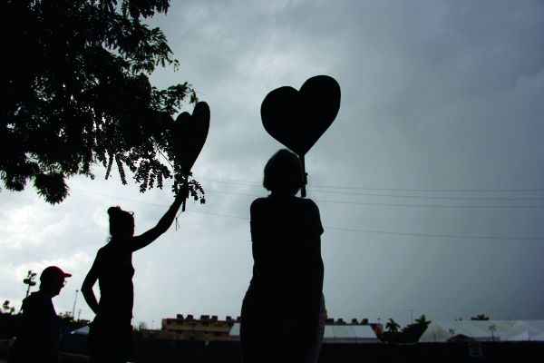 Protesters wave heart-shaped signs at children in the camp. (Tanvi Misra/CQ Roll Call)