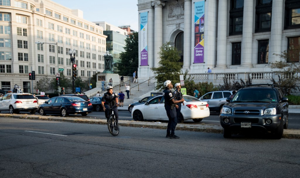 "UNITED STATES - SEPTEMBER 23: Police officers guide a SUV over the median on Massachusetts Avenue as Climate change protesters block the intersection of Massachusetts Avenue and North Capitol Street near the U.S. Capitol at rush hour on Monday, Sept. 23, 2019. A coalition of climate activists under the umbrella ""Shut Down D.C."" blocked intersections throughout DC to draw attention to climate change. (Photo By Bill Clark/CQ Roll Call)"
