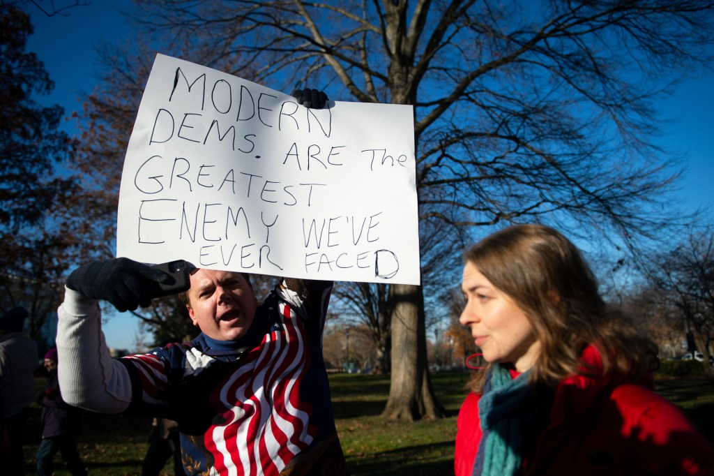 An anti-impeachment protester yells at pro-impeachment demonstrators on Wednesday outside of the Capitol. (Caroline Brehman/CQ Roll Call)
