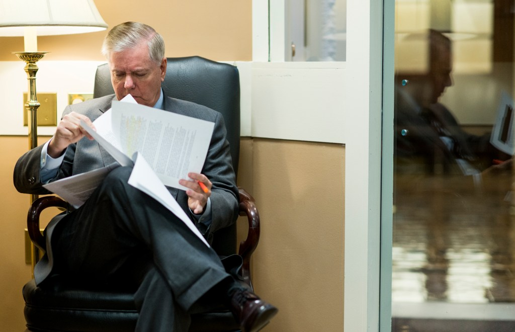 UNITED STATES - DECEMBER 9: Sen. Lindsey Graham, R-S.C., looks over the DOJ Inspector General's report on DOJ and FBI conduct during the FISA warrant process related to the 2016 presidential election in the Senate Radioa/TV Gallery before holding his press conference on the report on Monday, Dec. 9, 2019. (Photo By Bill Clark/CQ Roll Call)
