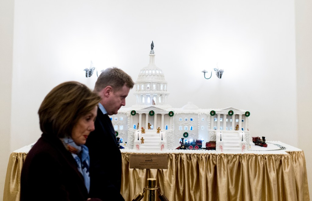 Speaker Nancy Pelosi, D-Calif., passes a Capitol gingerbread house as she arrives in the Capitol on Wednesday. The House of Representatives is scheduled to vote on articles of impeachment against President Donald Trump later in the day. (Bill Clark/CQ Roll Call)