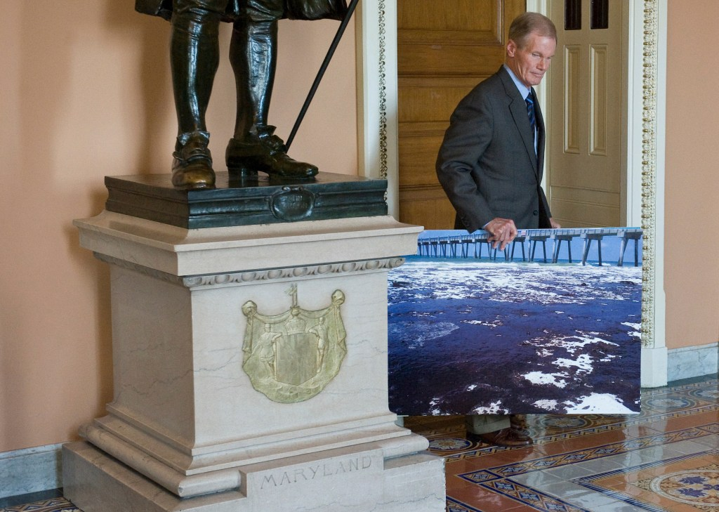 Sen. Bill Nelson, D-Fla., leaves the Senate Democrats' lunch on Thursday, June 24, 2010, with a photo of the oil spill affecting the Florida coast.