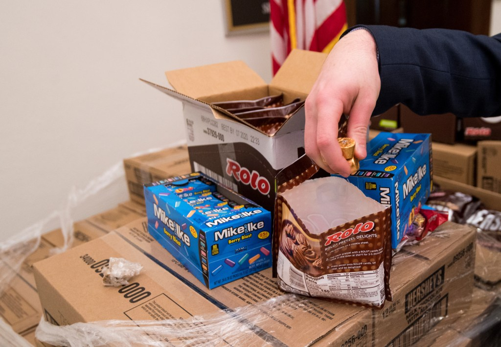 UNITED STATES - JANUARY 24: A reporter grabs a handful of Rolos from a pallet of Hersheys candy outside of office of Sen. Pat Toomey, R-Pa., on Friday, Jan. 24, 2020. The candy was sent by Hersheys to resupply Sen. Toomey's desk on the Senate floor, known as the candy desk, for the impeachment trial. (Photo By Bill Clark/CQ Roll Call)