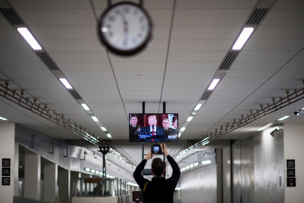 UNITED STATES - JANUARY 8: A photojournalist takes photos of the tv monitor in the Capitol's Rayburn subway stop as President Donald Trump speaks about Iran on Wednesday, Jan. 8, 2020. (Photo By Bill Clark/CQ Roll Call)