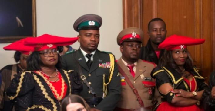 Members of the Namibian delegation listen as Herero chief Vekuii Rukoro speaks during a news conference March 16, 2017 in New York.  By DON EMMERT (AFP)
