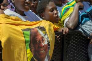 A supporter of Ramaphosa holds up a T-shirt featuring Zuma's expected successor