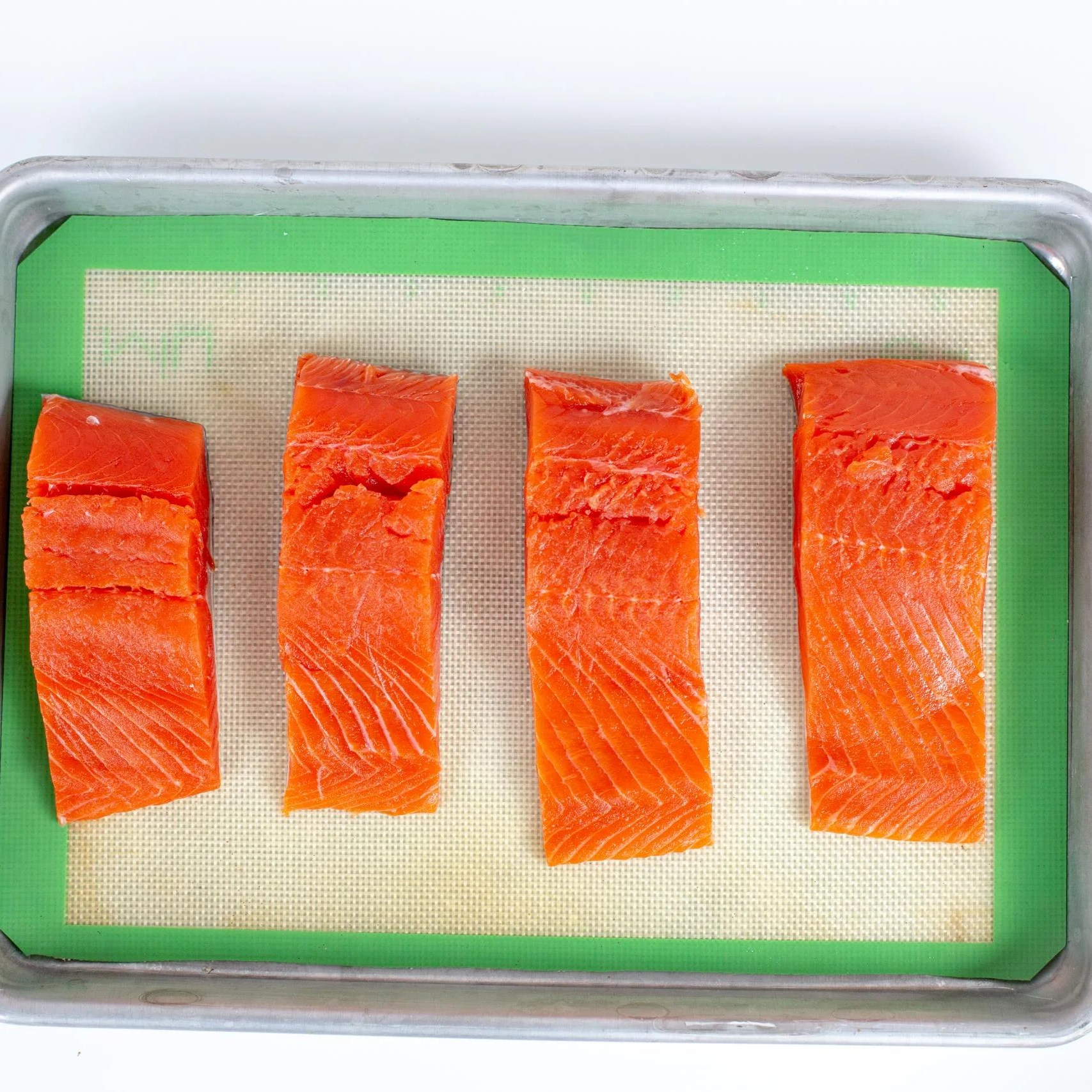 Salmon fillets on a baking pan lined with a silicon mat