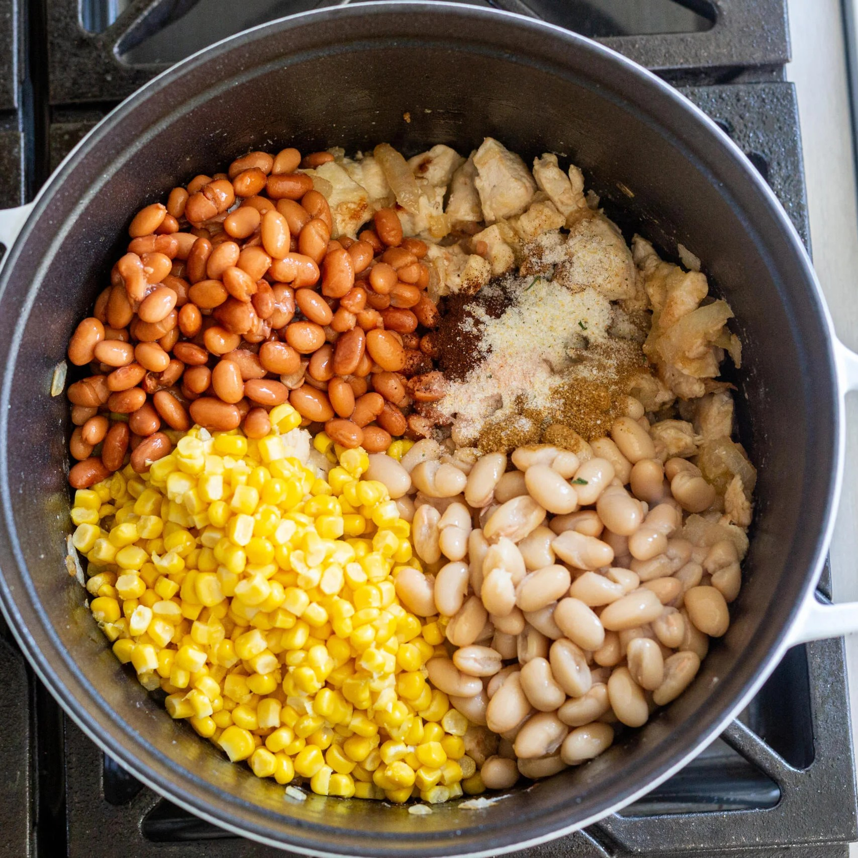 Beans and corn added to the pot with seasoning