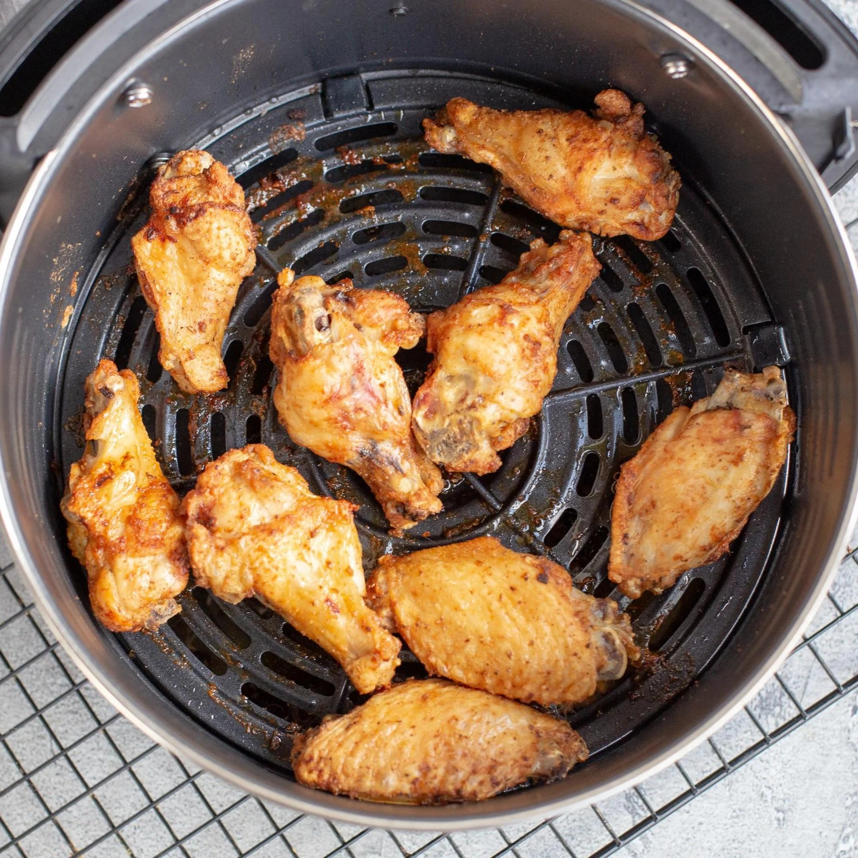 Chicken Wings in an air fryer that is on top of a baking rack