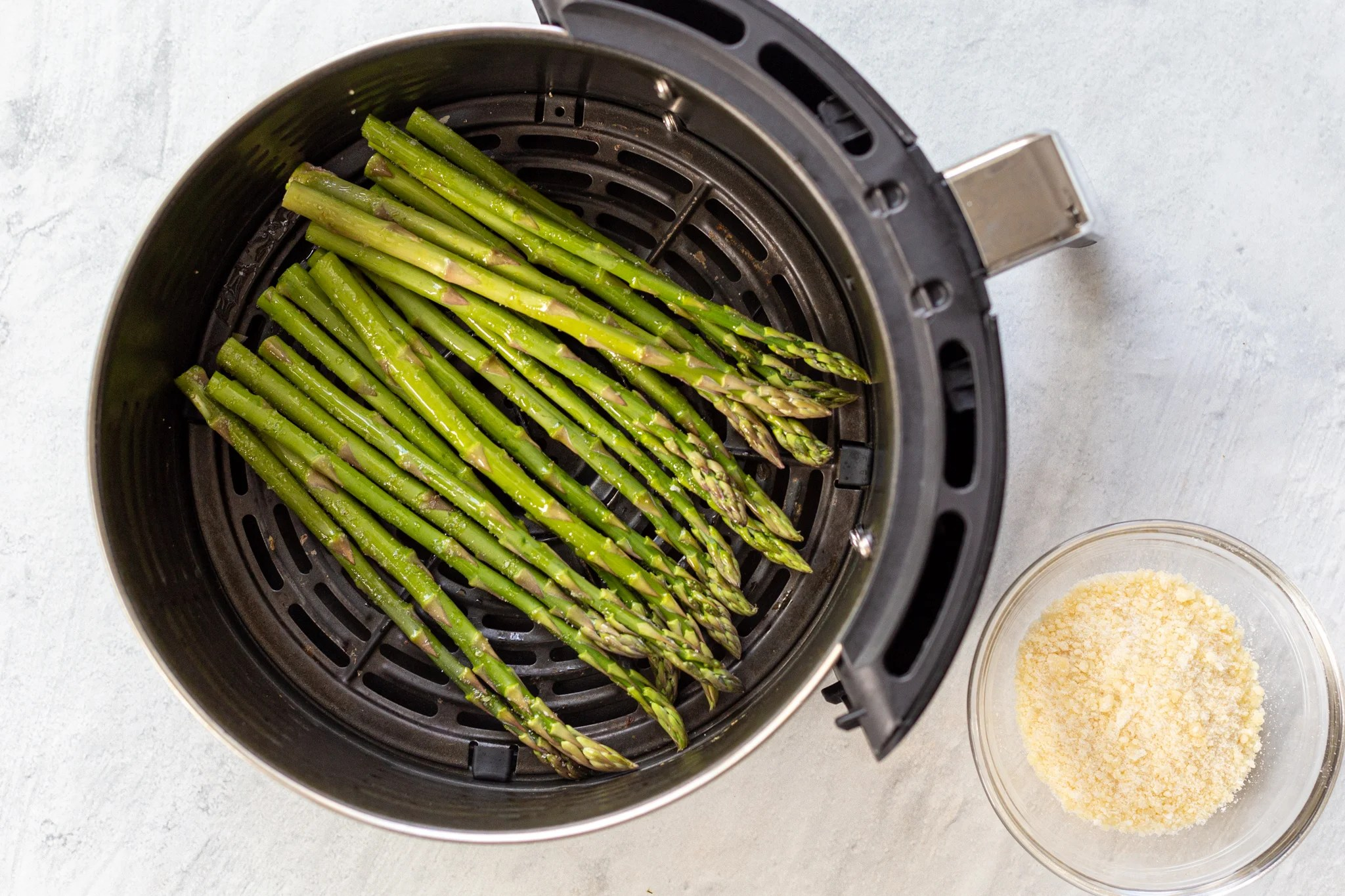 air fryer basket with raw asparagus
