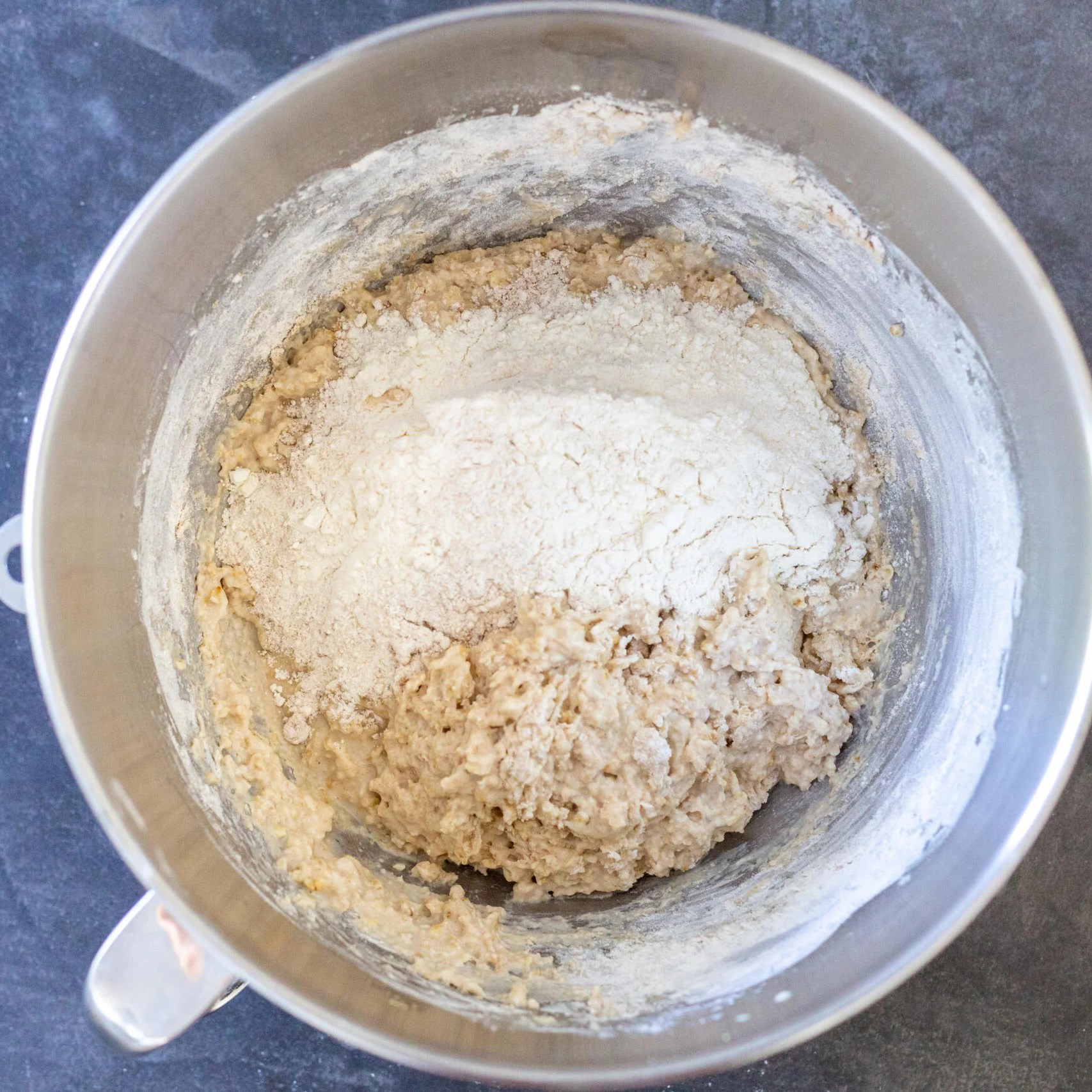 flour added to a mixing bowl with dough