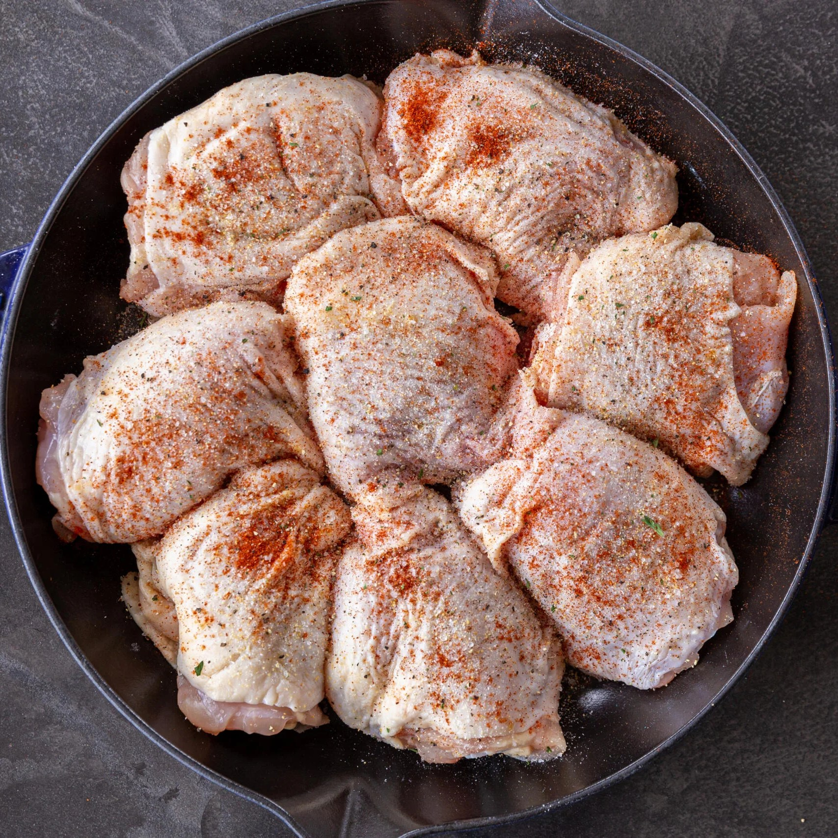 Seasoned chicken thighs in a pan