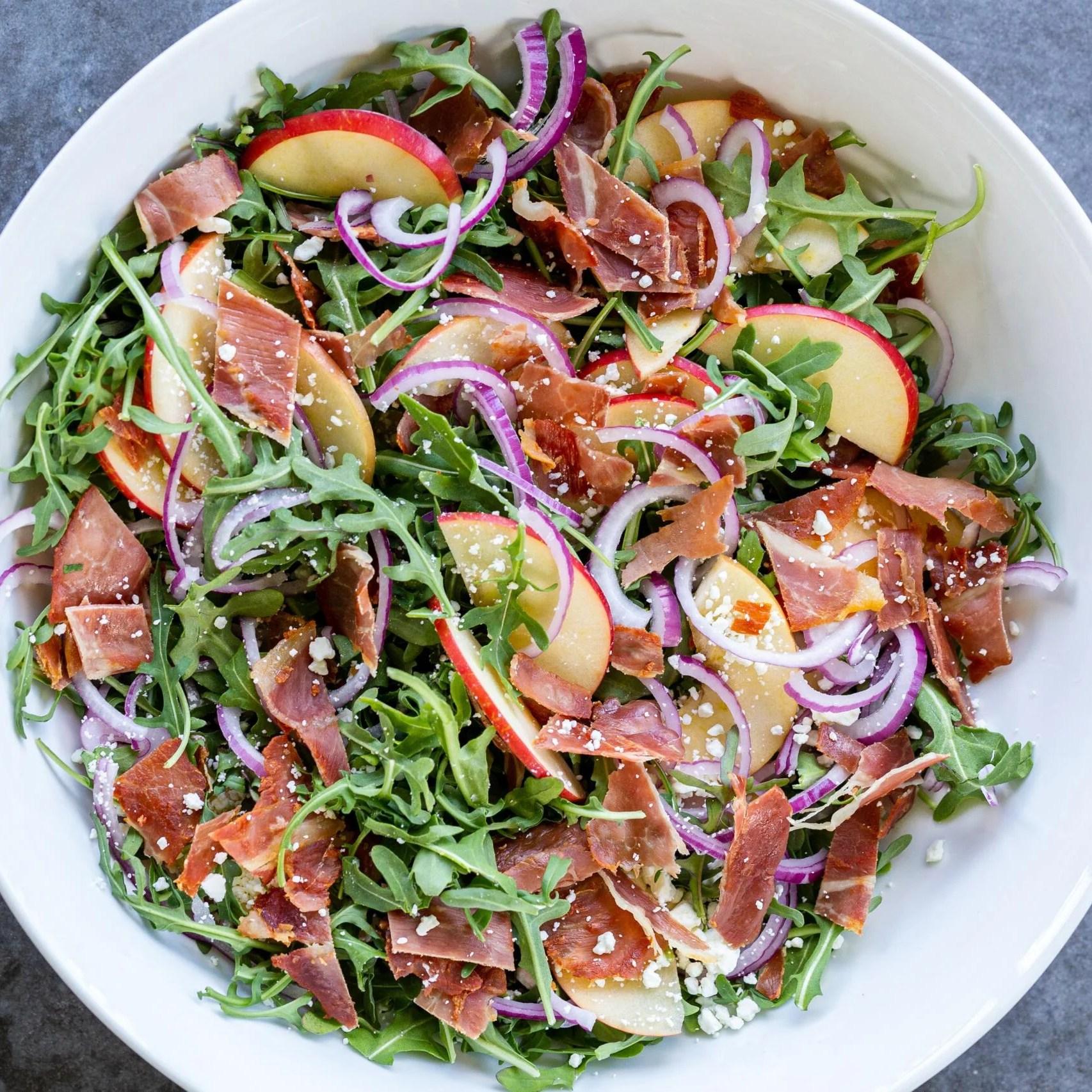 Arugula salad with prosciutto pieces on top