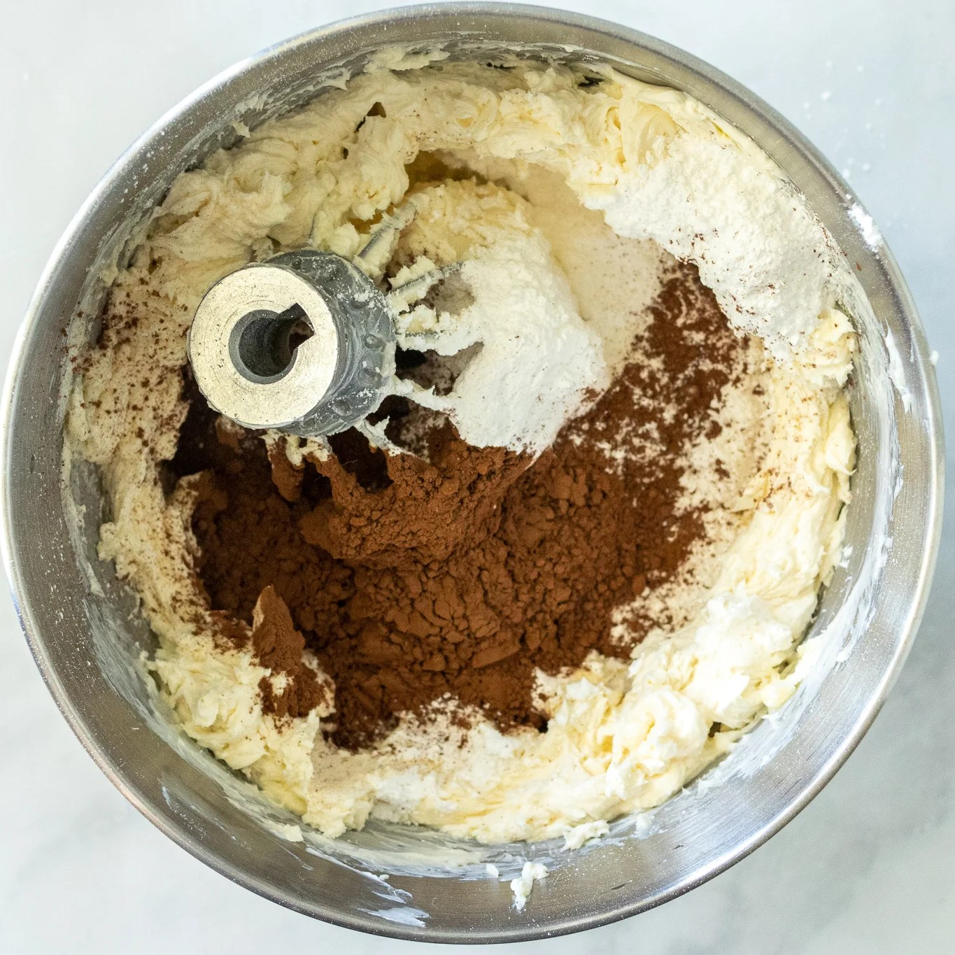 buttercream and cacao powder added to the mixing bowl