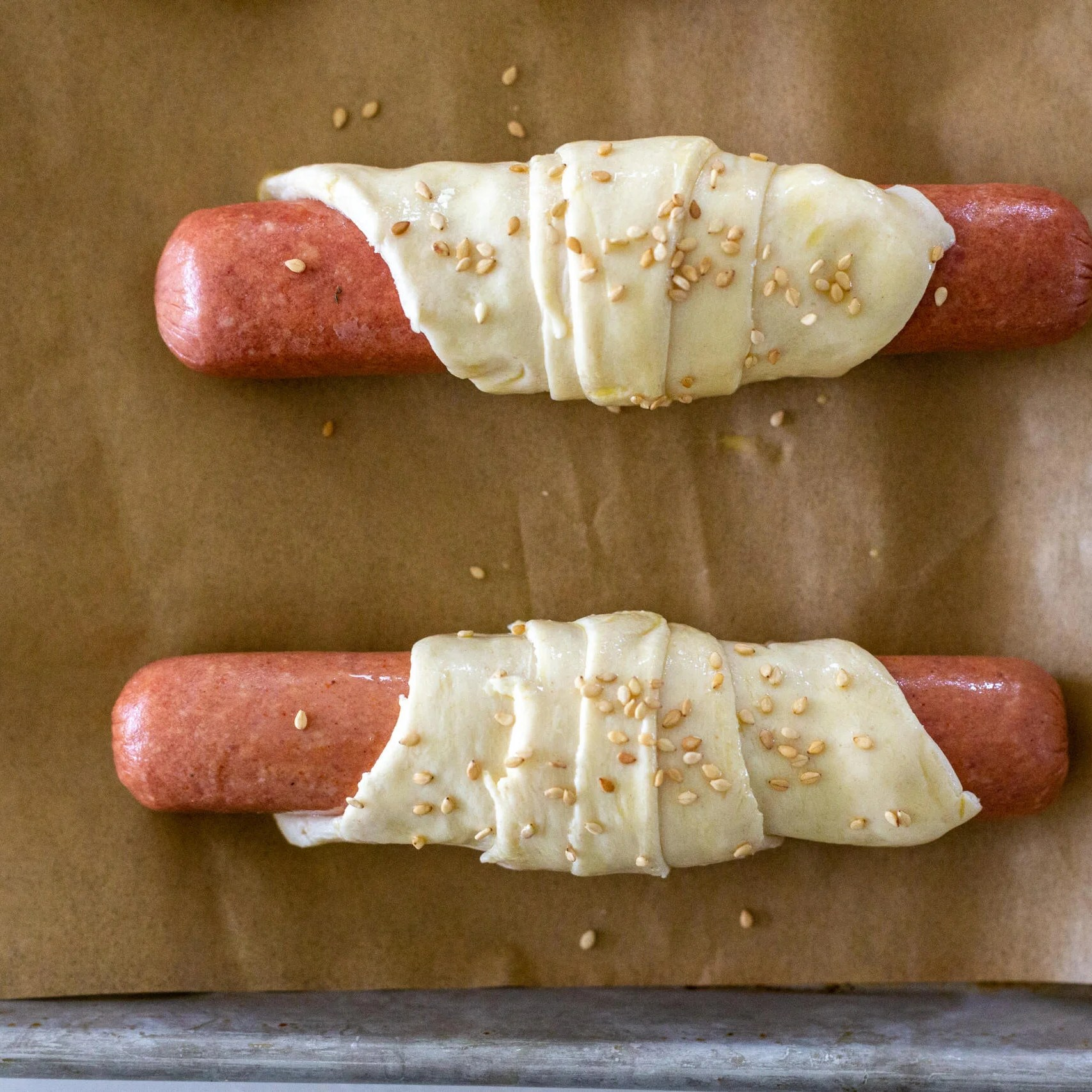 hotdog wrapped with dough ans sesame seeds sprinkles