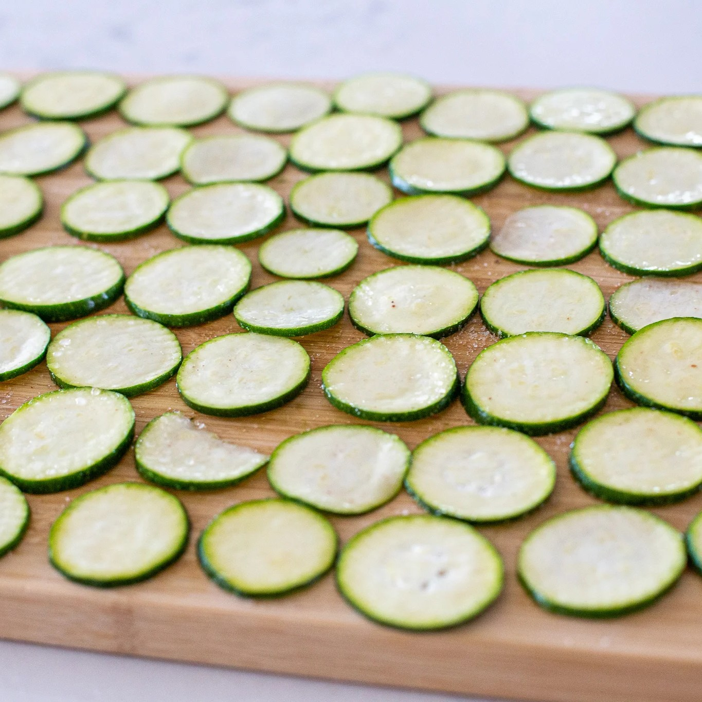 Salted zucchini pieces on a cutting board