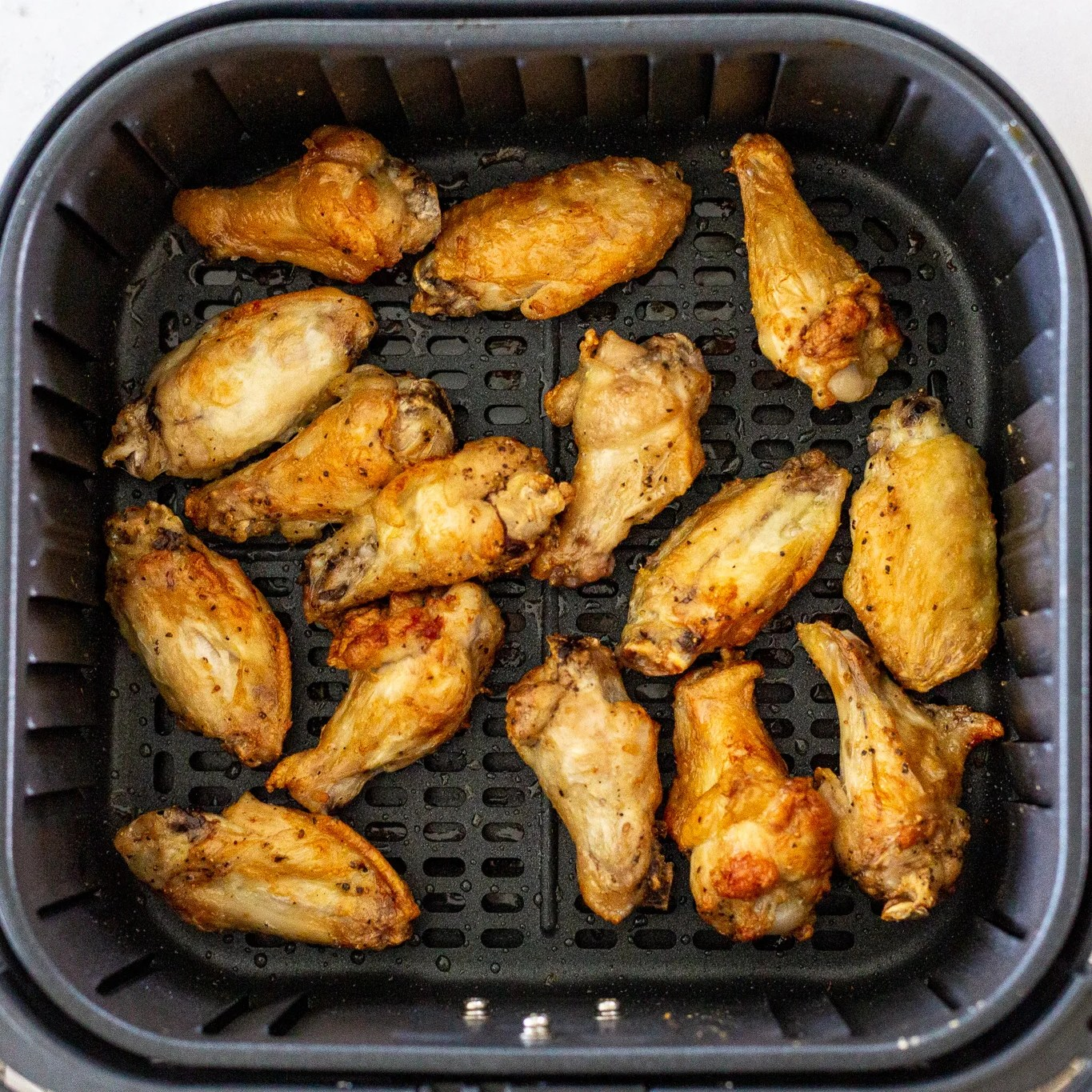 Cooked chicken wings in an air fryer basket