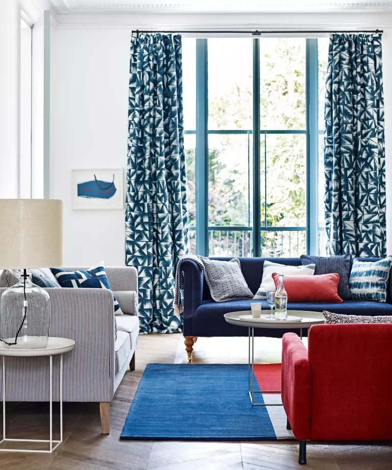 A living room curtain idea with white walls, dark blue patterned curtains and blue and red furniture