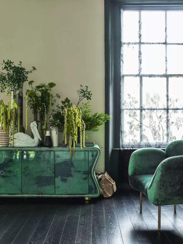 Green living room with black floorboards and green sideboard decorated with houseplants