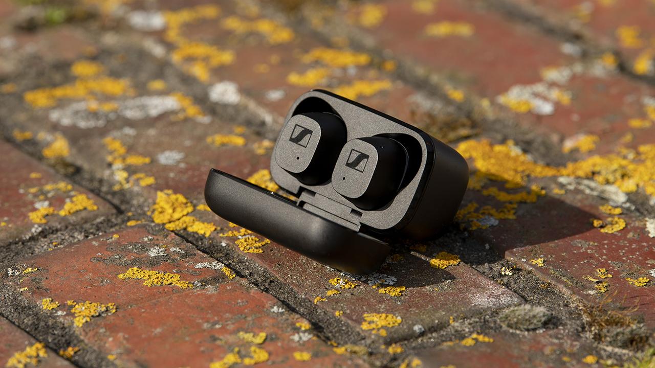 sennheiser cx true wireless earbuds in their charging case on a brick wall