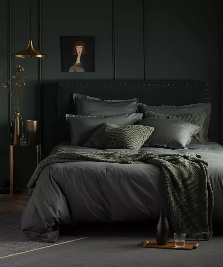 A bedroom with dark green painted walls and ceiling, and green bedding
