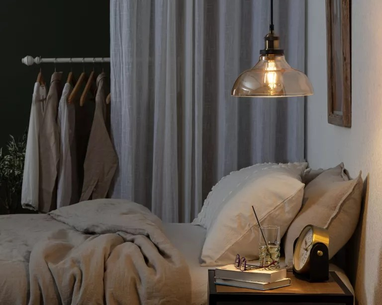 A bedroom with grey soft furnishings, a black wall, and a night light over the bed