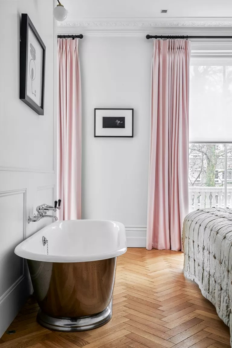 Bedroom with silver freestanding bath and long pink curtains