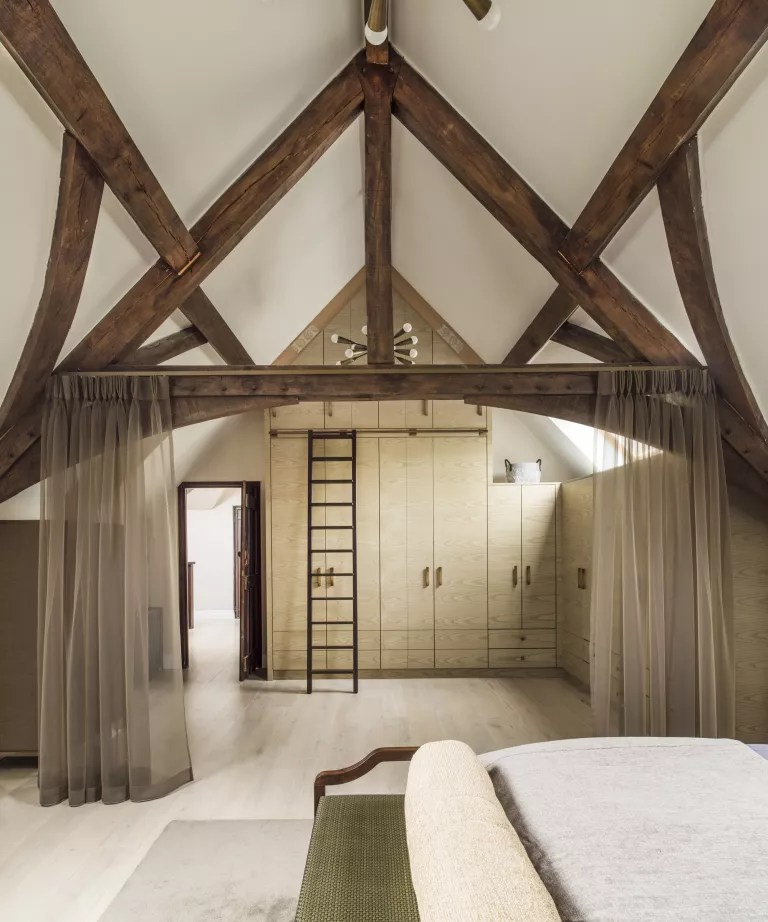 A bedroom with a beamed, vaulted ceiling and tall cabinetry with a ladder