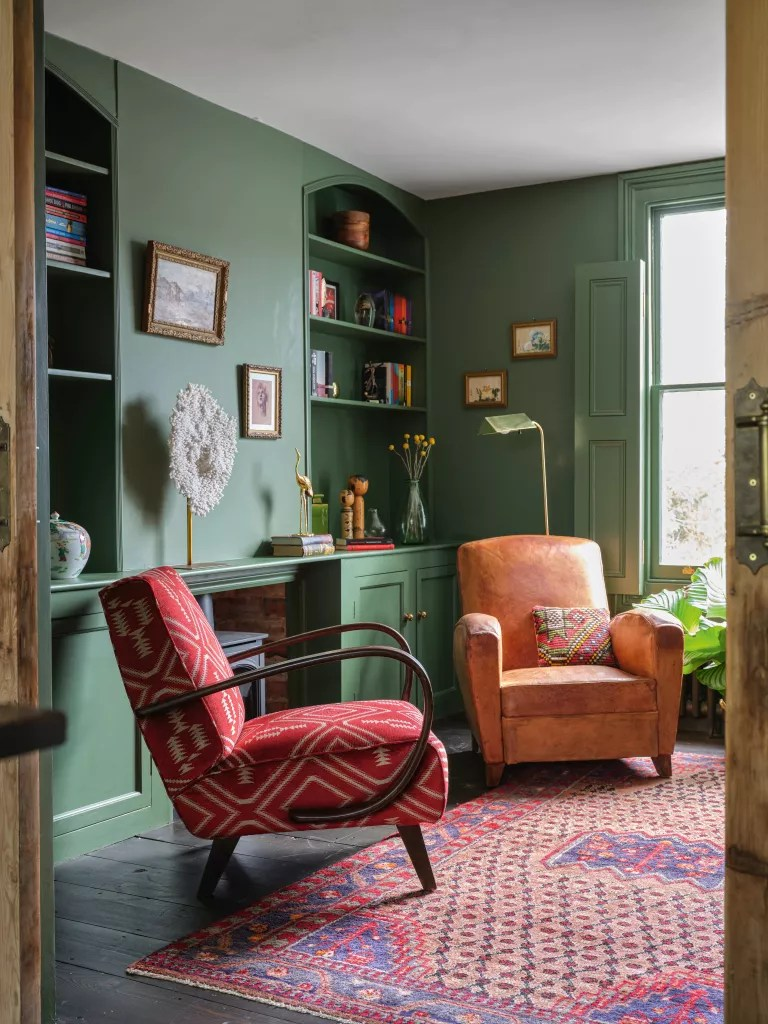 Green living room with built in shelving, armchairs and colorful vintage rug