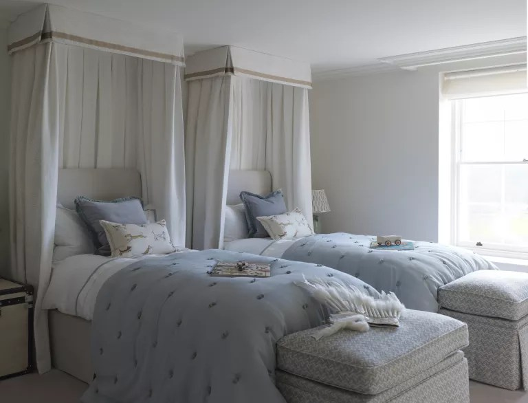 Twin beds with white canopies around a headboards and storage space at the ends of the beds showing hotel-style shared bedroom ideas.