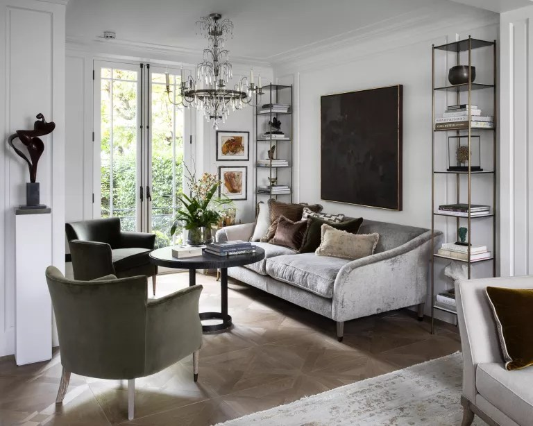 A living room with grey velvet sofa, white walls and dark green armchair
