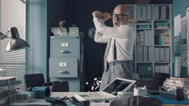 stressed businessman destroying his desk and laptop with a baseball bat