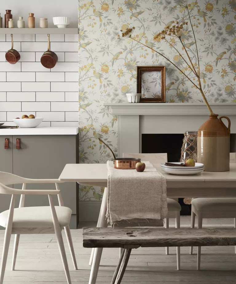 Fall mantel ideas with white and yellow floral wallpaper, white mantelpiece and simple white ceramic ornament with open frame decor