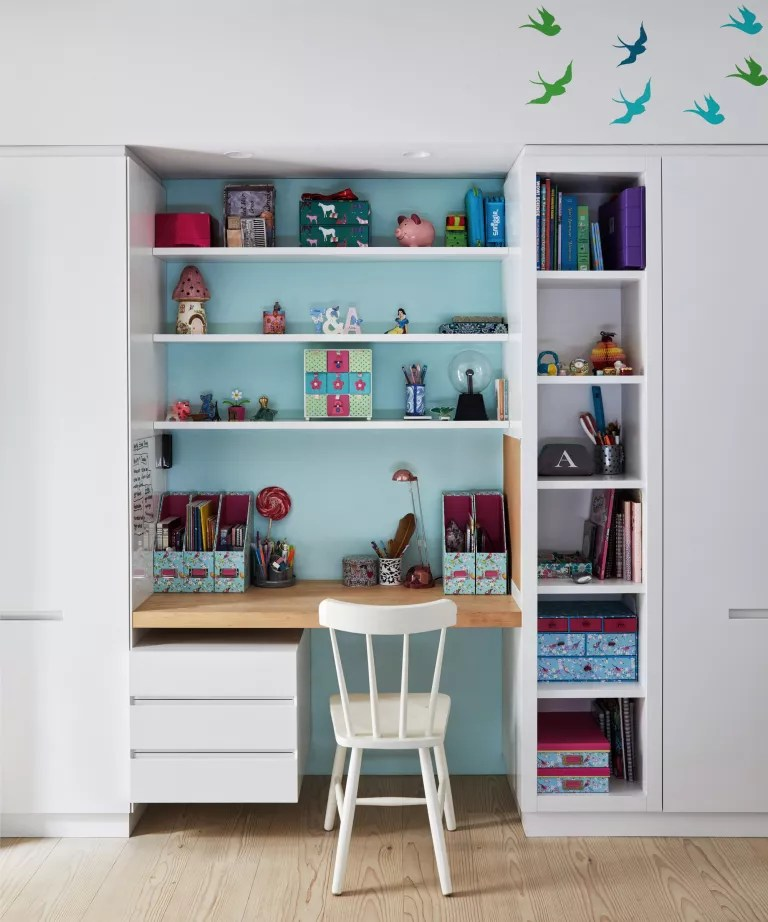 A child's bedroom with a recessed desk area picked out in pale blue paint against white surroundings