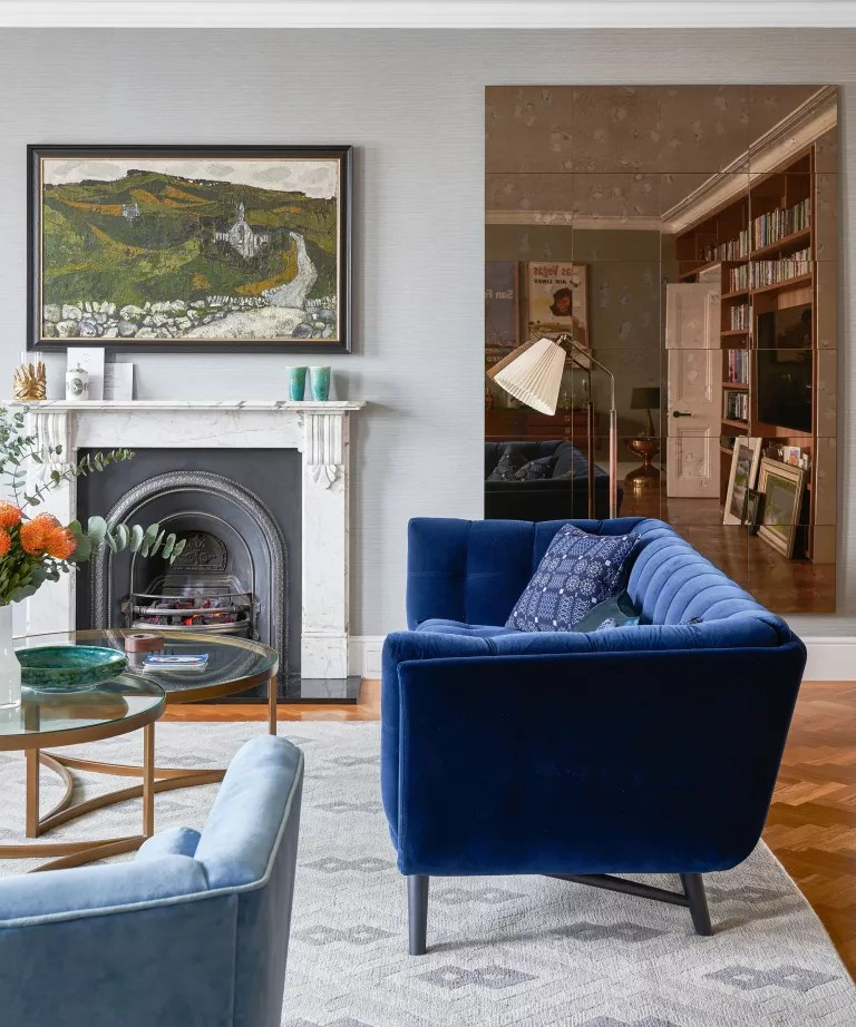 Living room with blue fluted sofa and mirror wall