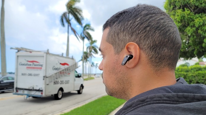 The reviewer wearing the Edifier NeoBuds Pro outside by a road on a which a truck is driving
