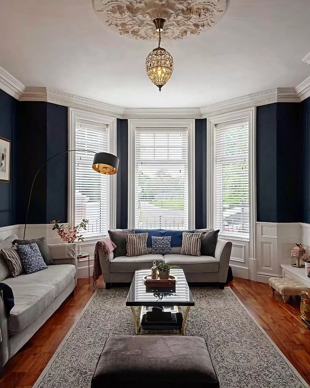 Blue living room with wooden floors neutral colored sofas and white bay windows with slatted white binds