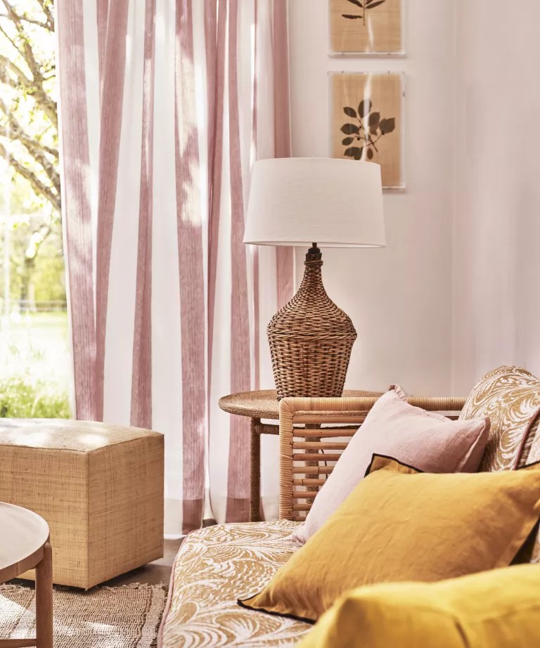 A living room curtain idea with pink and white striped fabric and yellow and rattan accessories