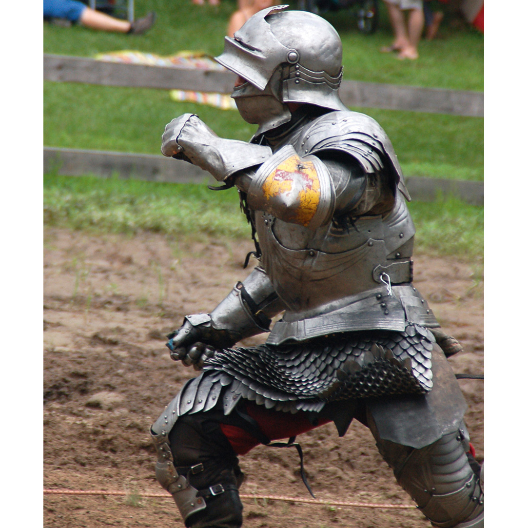 Photo of a person dressed in a knight's suit of armour in a battle enactment, with people sitting on the grass watching in the background