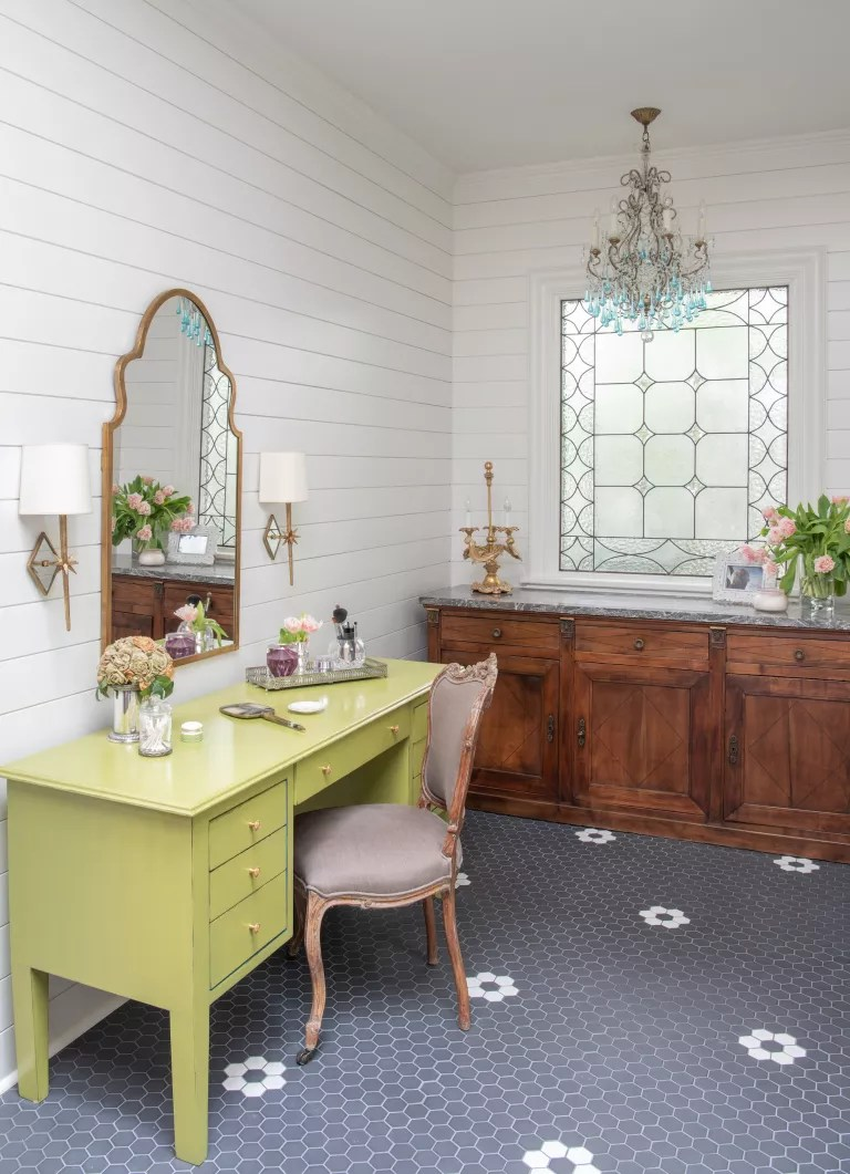 dressing room with bright yellow dressing table, grey tiled floor, gold mirror, vintage sideboard and shiplap walls