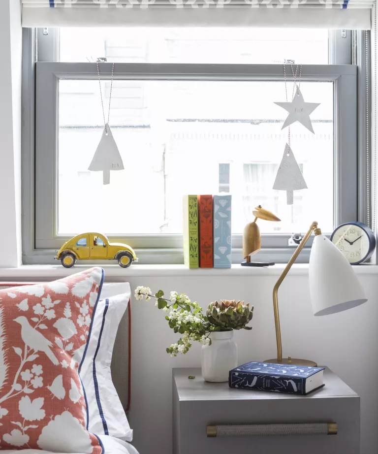A child's bedroom with neutral walls and furniture, colored furnishings