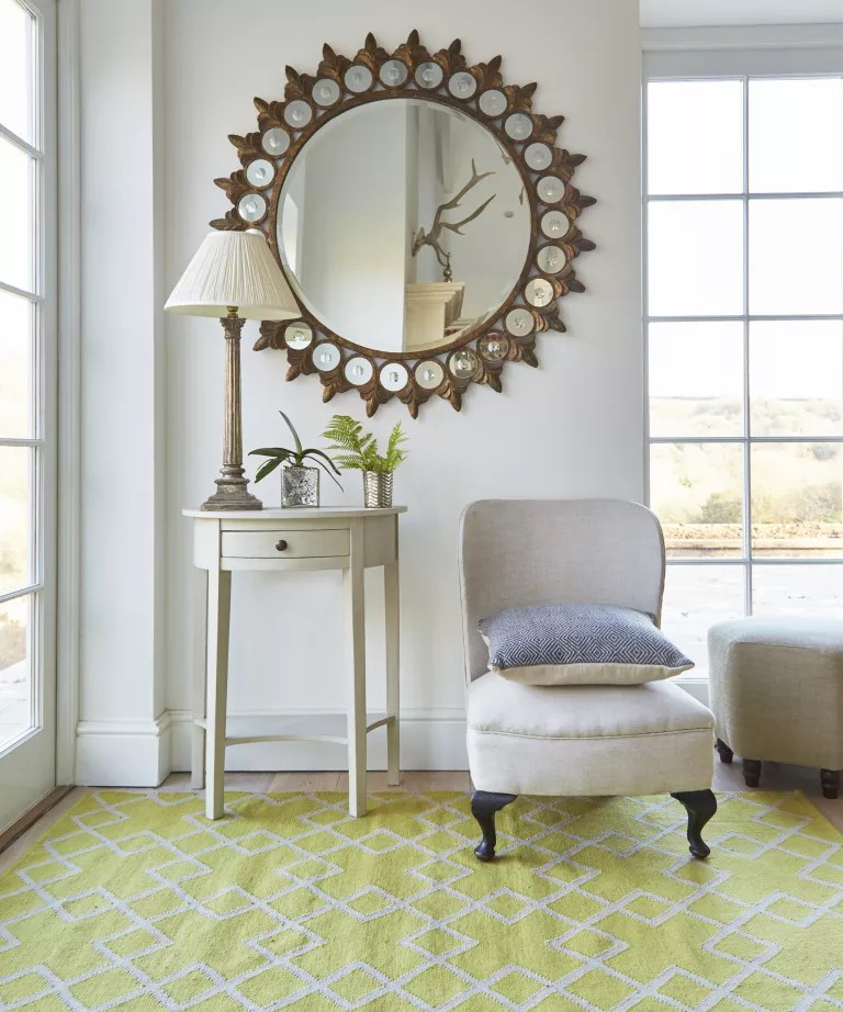 A living toom with large brass mirror and yellow rug
