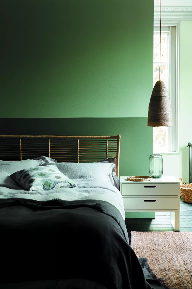 green bedroom with three shades of green painted on the walls, pale blond wood bedside