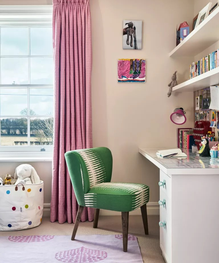 A child's bedroom with beige walls, pink patterned curtains and a green upholstered desk chair