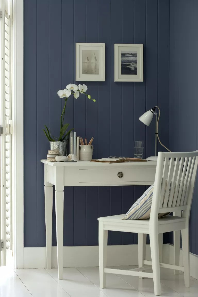 blue shiplap wall home office with white woodwork, white desk and white painted floorboards