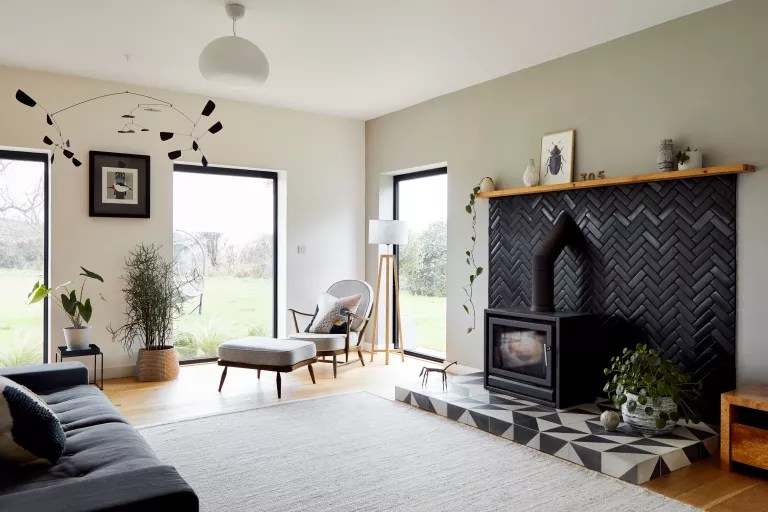 Living room with black herringbone tiled fireplace by Bert & May